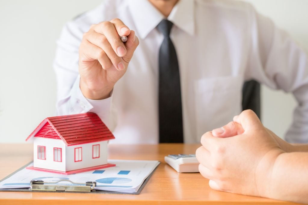 Home salesman stretches holding black pen, model house on wooden desk, Model house with red roof.
